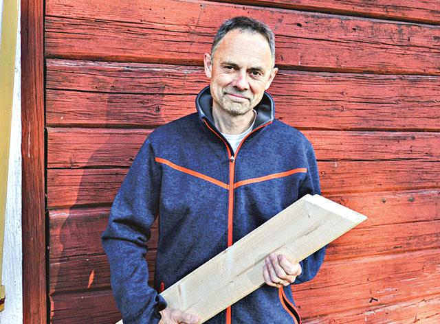 Trä är klimatsmart. Lars Vikinge med en nysågad planka framför en vägg av gammalt datum som står bra än idag.