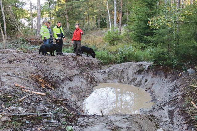 Carl Ankarstrand, skogsinspektör på Södra, pekar på den slamdamm som avslutar skogdiket, för att inte slammet ska rinna ut i sjön Tjen som skymtar i bakgrunden. Han inspekterar jobbet tillsammans med entreprenören Daniel Heran, samt skogsägarna Christina och Thomas Béen.