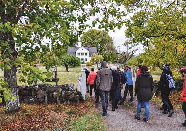 Sällskapet på väg in i trädgården. Mangårdsbyggnaden på Tinnerö gård syns i bakgrunden.